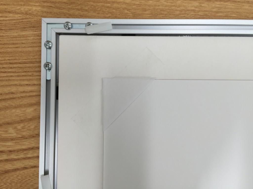 印画紙の四隅を三角の紙と額装テープで固定